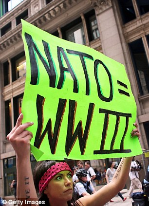 An Occupy Wall Street protestor prepares for the arrival of NATO (left) as another protestor faces-off against police (right)