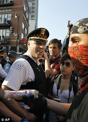 An Occupy Wall Street protestor prepares for the arrival of NATO (left) as another protestor faces-off against police (right) with a pack of donuts