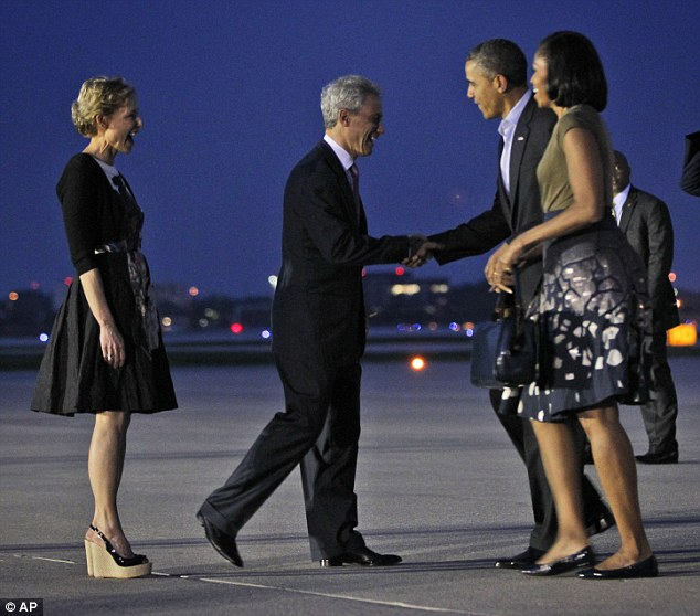 President Barack Obama and first lady Michelle Obama are greeted by Chicago Mayor Rahm Emanuel, center, and wife Amy Rule, during their arrival at O'Hare International airport in Chicago