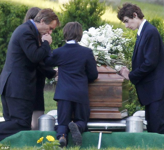 Prayer: Mr Kennedy and his children kneel to remember Mary at the cemetery on Saturday afternoon