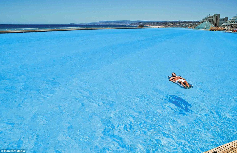 Lost at sea: A bather floats on the amazingly clear waters of the vast Crystal Lagoon, at the San Alfonso del Mar resort, Chile