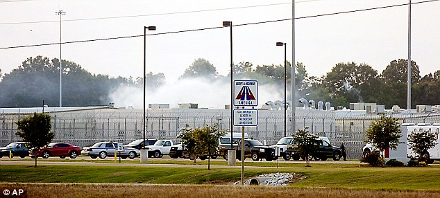 Melee: Smoke rises above the Adams County Correctional Center in Natchez, Mississippi yesterday