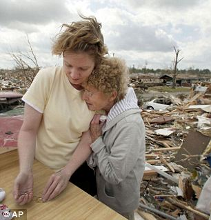 Staying strong: Debbie Surlin is hugged by her mother Beverly Winans (left) in the wake of the twister and now the land stands clear of any debris