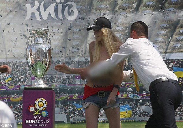 Stunt: A topless activist from the group - with an anti Euro 2012 slogan on her belly - had also tried to grab the trophy from Independence Square in Kiev earlier this month