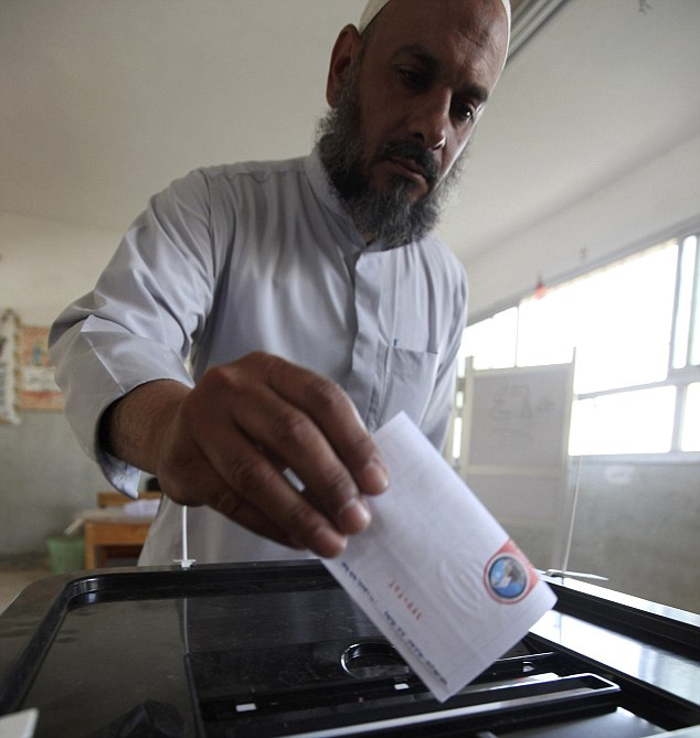 Historic moment: An Egyptian man casts his vote inside a polling station in Cairo in the country's first free and fair presidential election