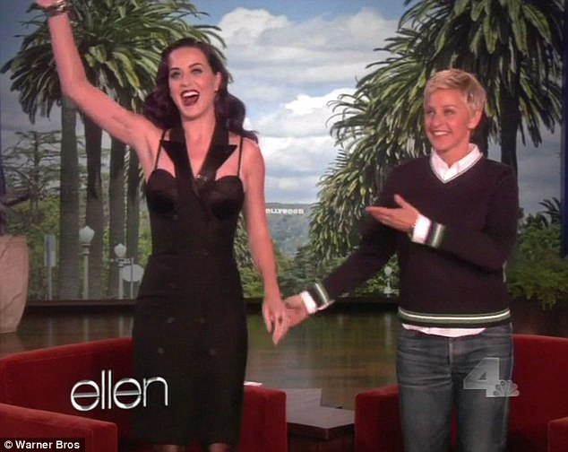 Striking: Katy sported a clinging back dress, dark lipstick and newly purple hair for the interview