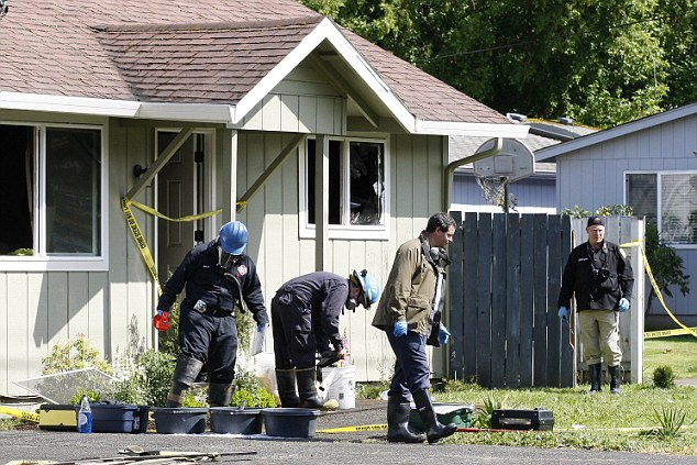 Investigators search in the front yard of a home where the bodies of the woman and children were discovered