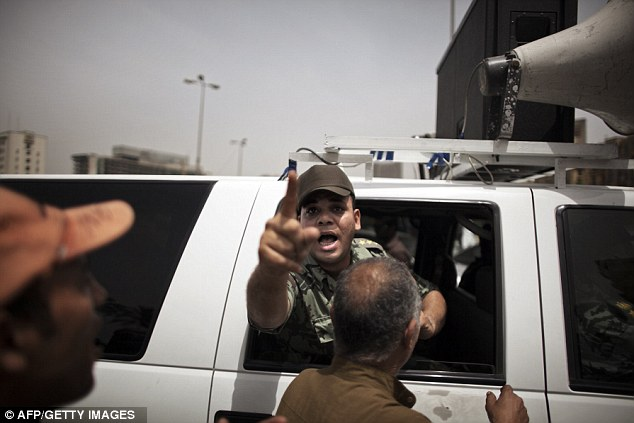 An army officer gestures as he and colleague ride in a vehicle with a megaphone calling Egyptians to vote