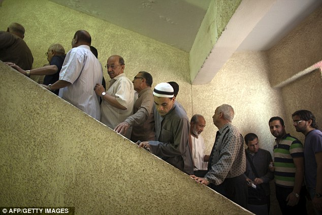 Stepping up: Egyptian men line up to vote at a polling station in Cairo