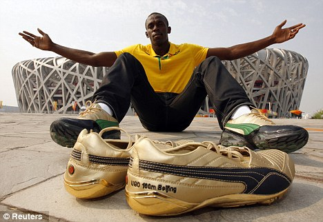 Golden touch: Usain Bolt with his Puma shoes outside Beijing's Birds Nest Stadium