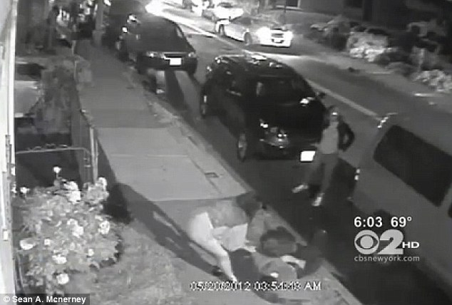 Stripped: A woman hovers over the unconscious man as she removes his chain in full view of CCTV