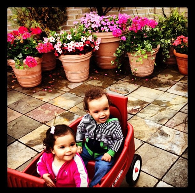 Wagon-riders: Mariah's husband of four years, actor Nick Cannon, shared the second image of little 'Roc and 'Roe riding in a red wagon near potted flowers on an outdoor patio