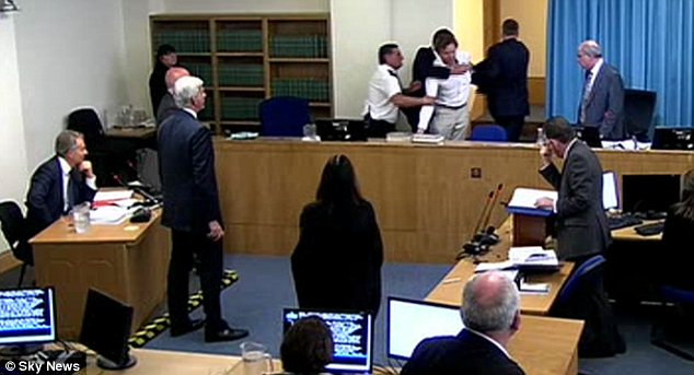 Bundled out: Tony Blair (far left) appeared unfazed by the disruption. Lord Justice Leveson (standing to the right of the commotion, did not. Robert Jay QC (standing below Leveson) held his head in his hands