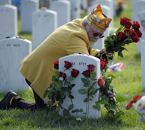 Making the rounds: John Ryan places roses at a grave of a solider he did not know in Arlington National Cemetery on Memorial Day in advance of President Barack Obama's visit