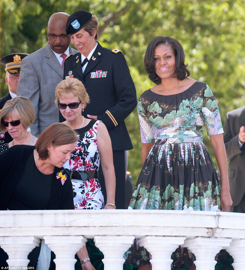 Celebratory: Though the mood was somber throughout the Arlington service, Mrs Obama finds a lighter note at one point while she was leaving after hearing her husband's remarks