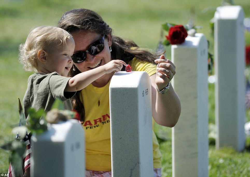 Remembering family: 17-month-old Rachel Crosby puts a heart trinket on her uncle Staff Sargent Nick Sprovtsoff's, who died at age 28 in the Iraq War, grave wile her mother Tracey Crosby helps