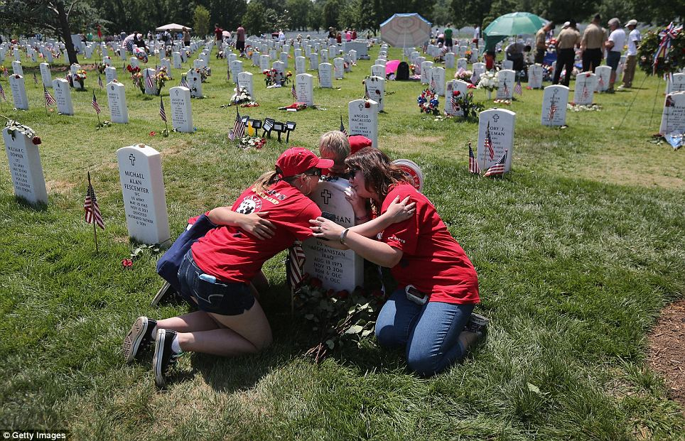 Group hug: Leanne McCain (right) and her children traveled from North Pole, Alaska to hug the tombstone of her husband and their father Johnathan McCain who was killed by an Afghan roadside bomb