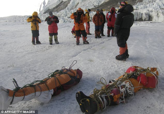 Recovered: This photo from May 2010 shows sherpas receiving two corpses from near Everest's summit