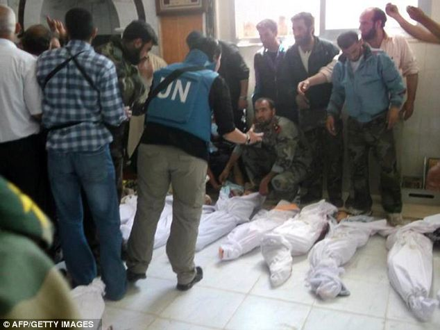 International attention: UN observers view bodies at a hospital morgue before the burial of the Houla dead