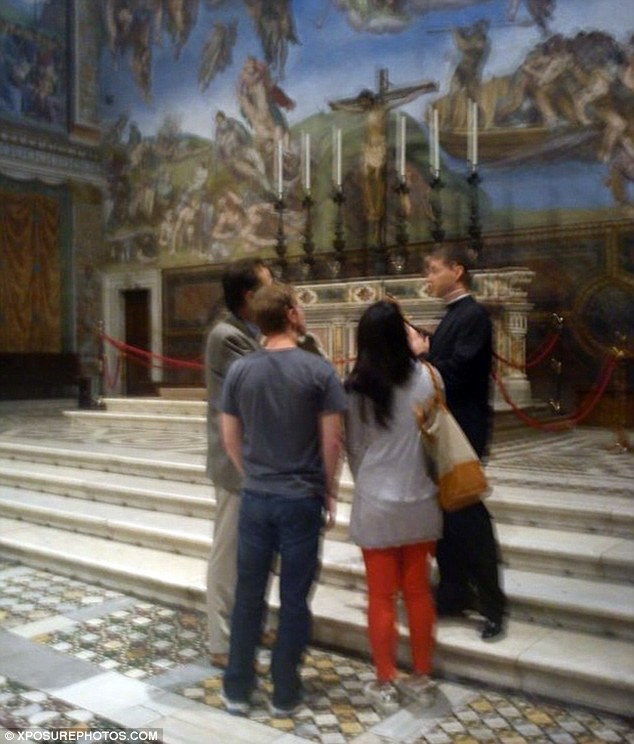 Tourist trail: The couple were casually dressed in jeans and t-shirts as they listened to a priest talk about Michelangelo's art