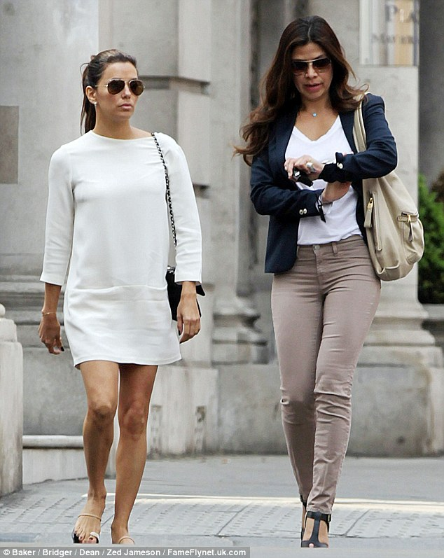 London's calling: Eva Longoria slipped into a Sixties-style white minidress to take in the sights of London today with a friend