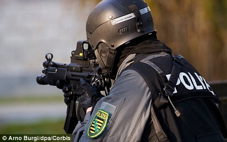 Attack: SWAT teams swooped on the scene after the man brandished a 12-inch kitchen knife at police officers. They subdued him with beanbag projectiles