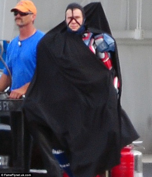 Under wraps: Badge Dale made his way to the set with a giant black cape covering his outfit