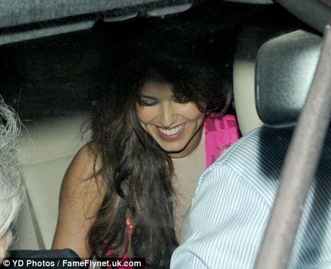 What are you smiling at? Cheryl beams as she leaves the nightspot in a taxi