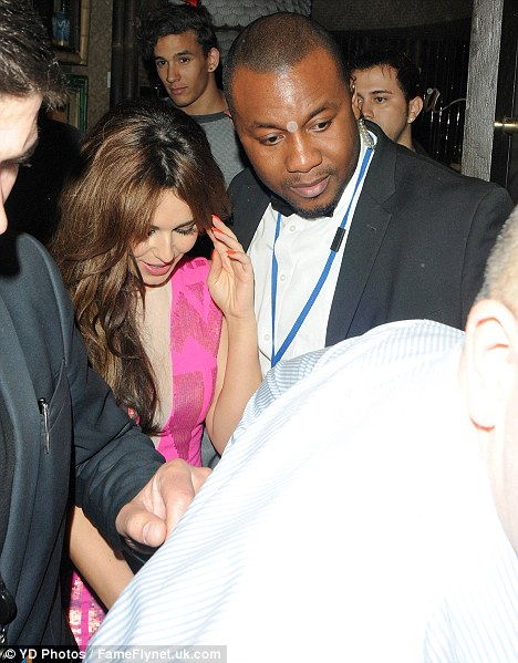 Through the crowds: Cheryl is easy to spot in her bright pink dress