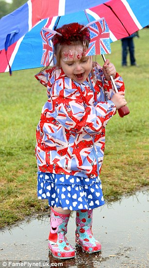 Three-year-old Leilah Palmer doesn't let the bad weather spoil her fun at the Jubilee Family Festival in Hyde Park, London