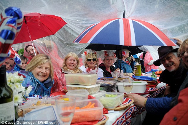 Save our scones: Plastic sheeting forms a makeshift shelter for party guests in Oxfordshire as the rain lashes down