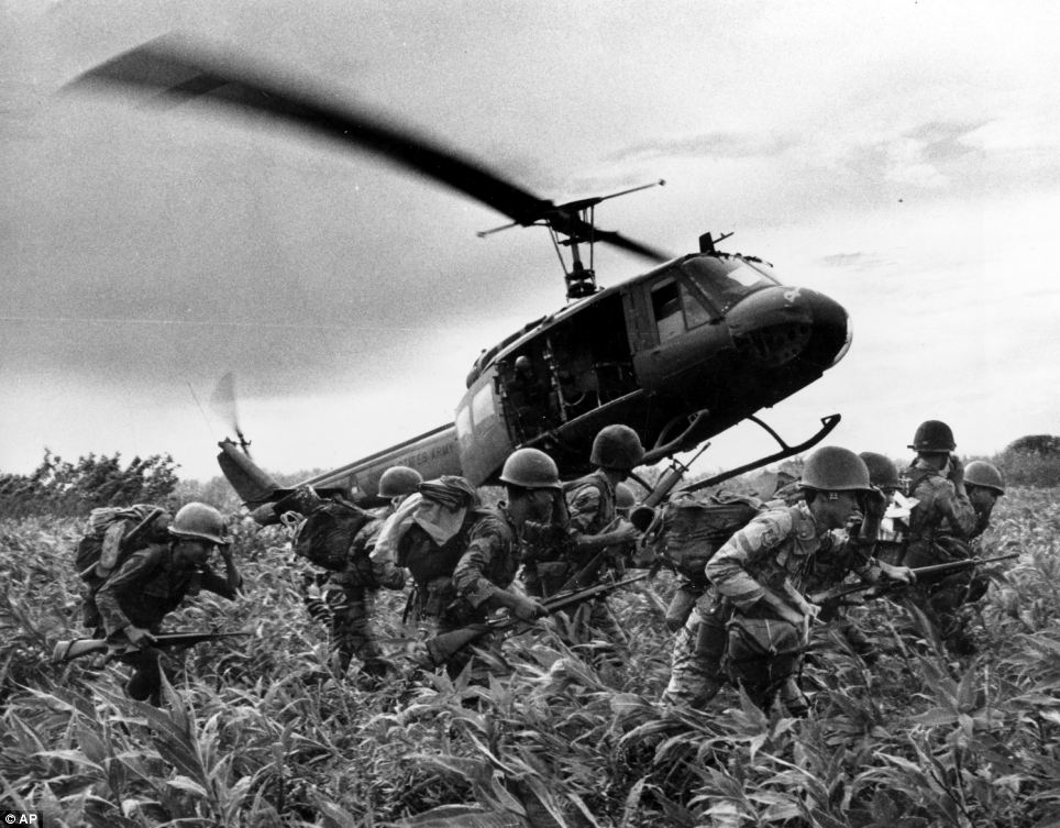 Vietnamese Marines rush to the point where a descending U.S. Army helicopter will pick them up after a sweep east of the Cambodian town of Prey-Veng in June 1970