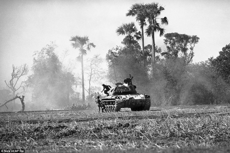 Trees are ravaged in the background to this picture of a South Vietnamese tank crew as the soldiers inside abandon it after being hit by B40 rockets and automatic weapons two miles north of Svay Rieng in eastern Cambodia