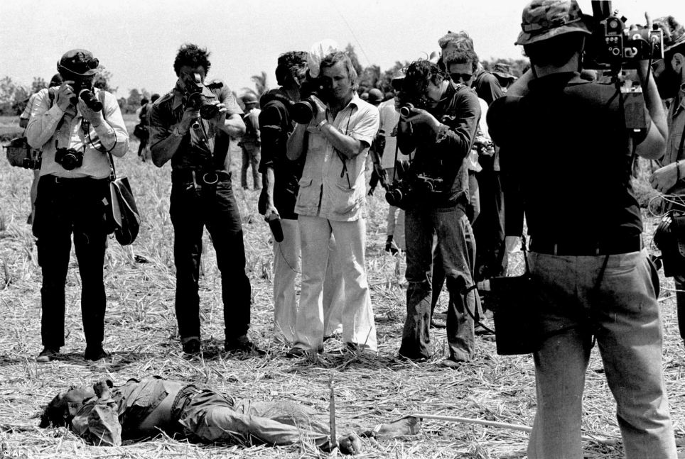 Never far from devastation, Nick Ut took this picture of journalists photographing a body in the Saigon area in early 1968 during the Tet offensive
