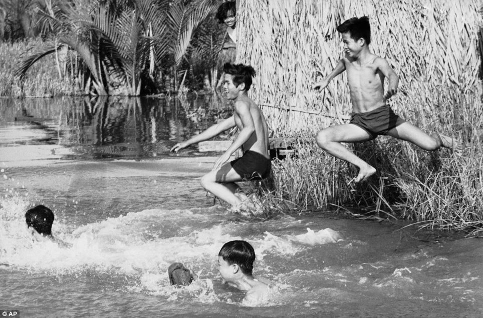 Spending so much time with members of the military he also got time to picture them having fun. Here he pictured youthful civil defence militiamen leap into the flooded Nipa Palm grove near Saigon on April 6, 1969