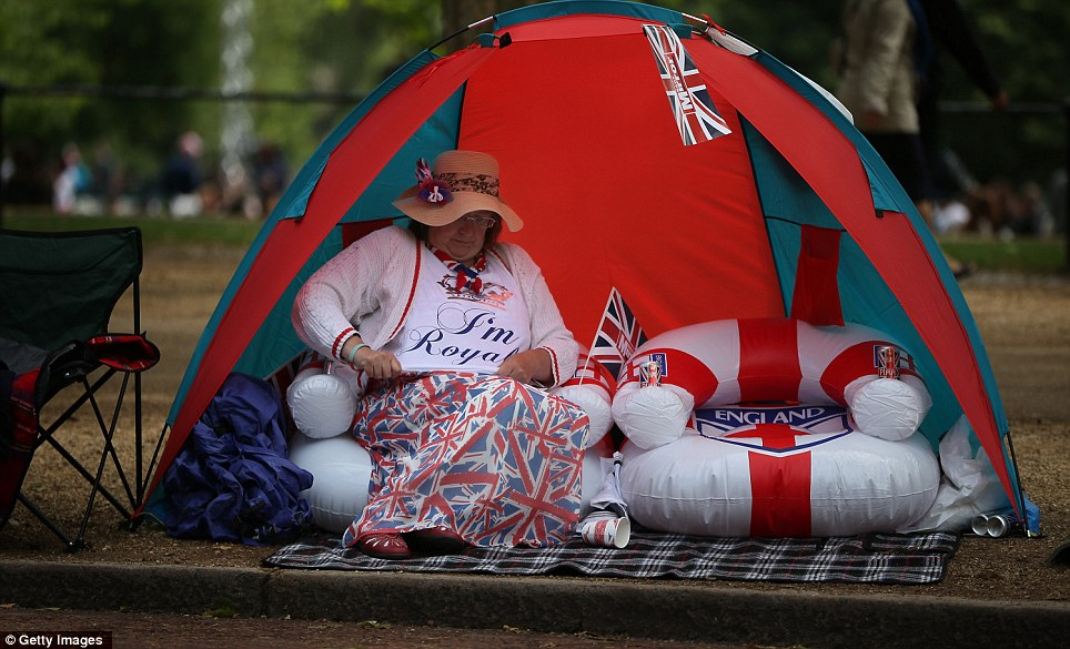 A woman sits in a tent in The Mall on a blow up chair complete with Union Flag themed flags and rug