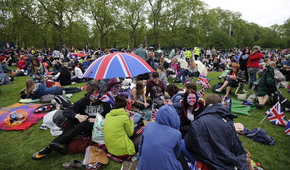 Umbrellas at the ready: Crowds gather on the grass in St James' Park ahead of the Queen's Diamond Jubilee Concert