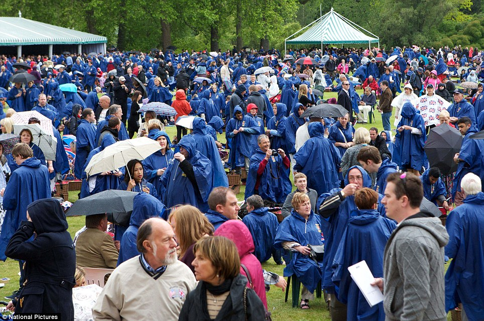 Protection: Fans take shelter from the rain under special Jubilee Ponchos in the gardens of Buckingham Palace