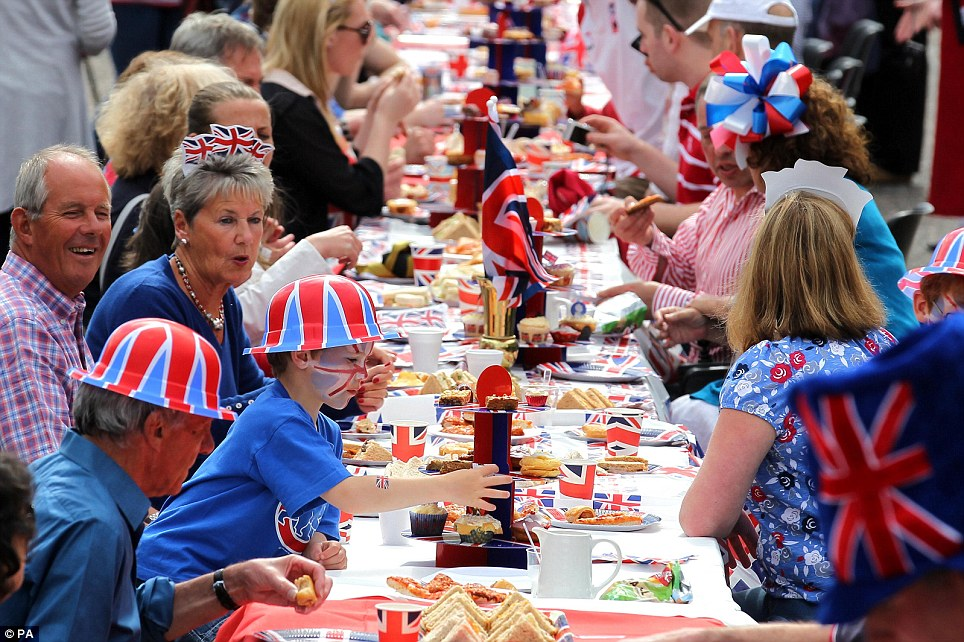 Five-year-old Harry Nussey takes a cake from the table as residents of Murrayfield Drive in Edinburgh sit down for their Jubilee street party