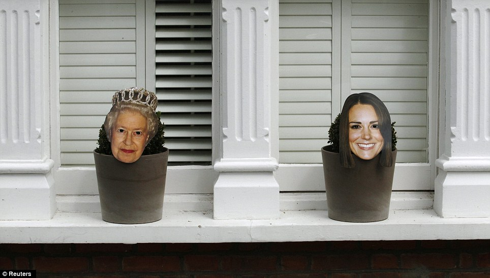 Plant pots are decorated with masks of Queen Elizabeth and Catherine, Duchess of Cambridge, at the Goldsmith Avenue Street Party in Ealing, west London