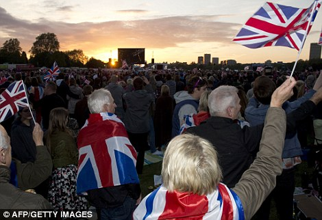 People wave flags in Hyde Park during a live retransmission of the Diamond Jubilee concert