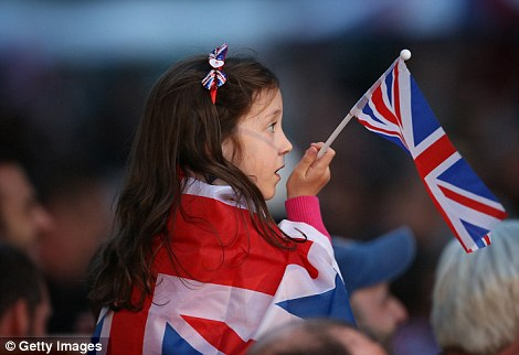 A girl wearing and holding a Union Jack flag watches the Diamond Jubilee Concert from the Mall