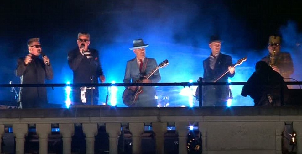 Madness perform Our House on top of Buckingham Palace, while the building provides a backcloth for a moving picture show to illustrate the song