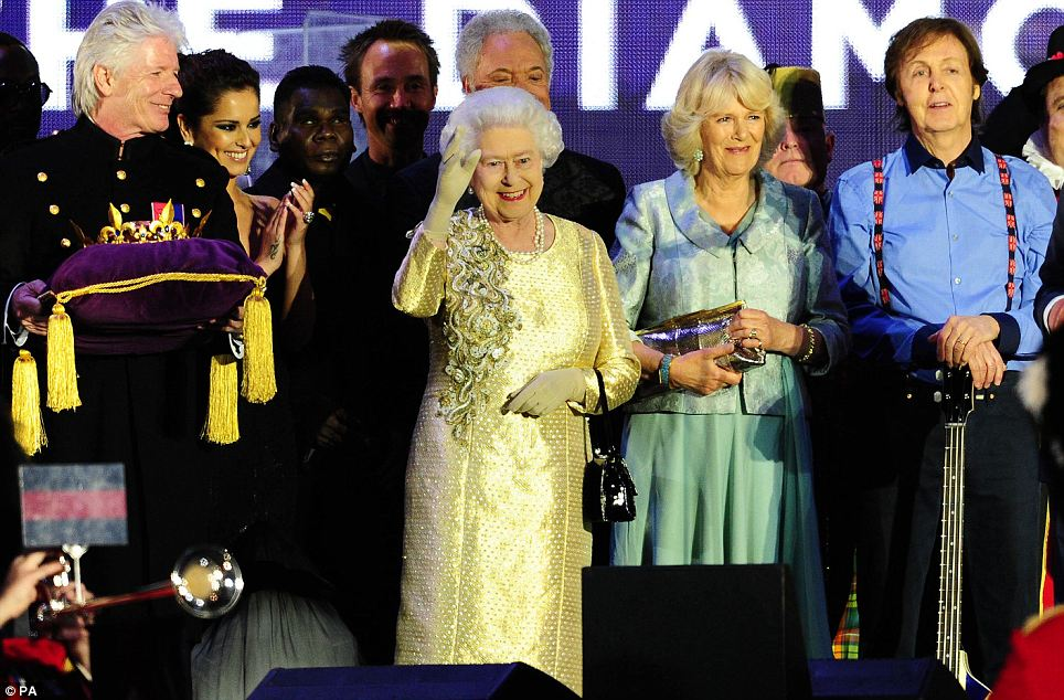 The Queen waves to the crowd while on stage outside Buckingham Palace during at the end of the Diamond Jubilee Concert