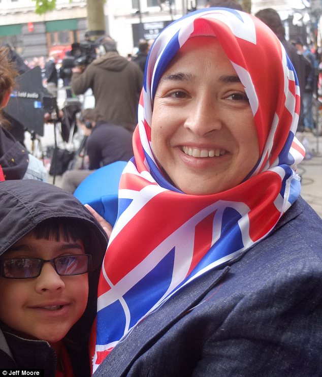 Proud: Yasmin Majid wears a union jack head scarf as she waits in the crowd with her children Adnan and Misbah outside St Paul's Cathedral for the Queen's Jubilee service