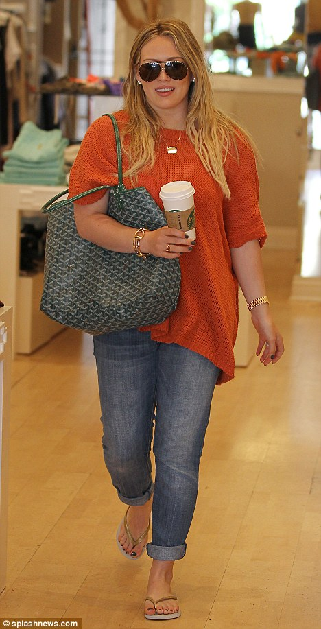 Covering up: Hilary Duff stepped out in a baggy orange knit while shopping at Switch Boutique in Beverly Hills