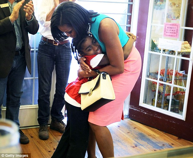 Six-year-old Sydney Trapp hugs the First Lady as she visits the bakery in Occoquan, Virginia, yesterday