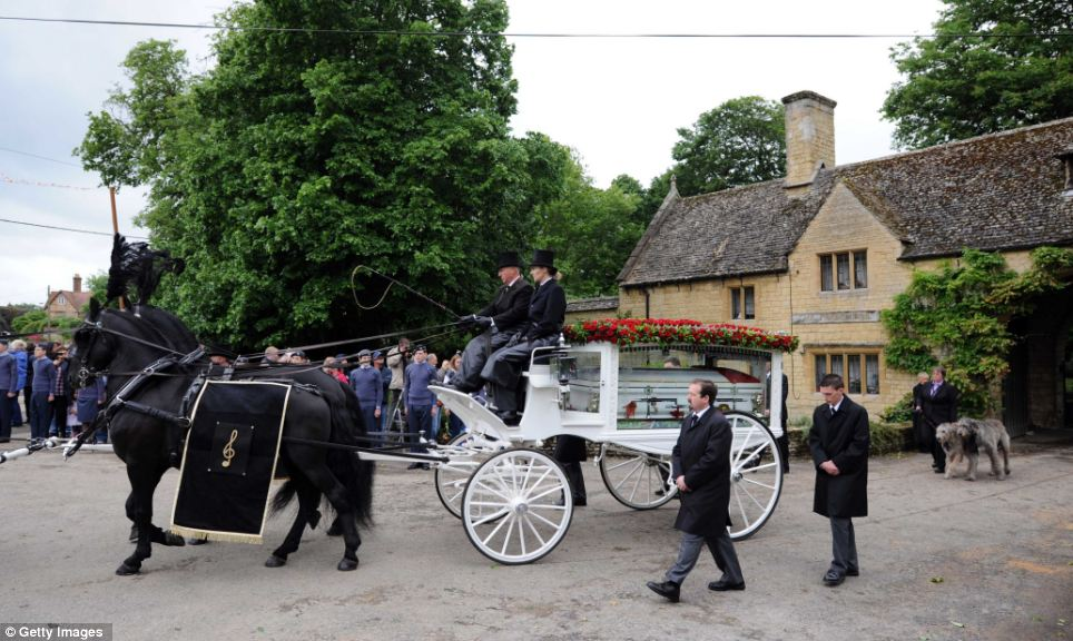 For the last time: Gibb's casket leaves his Oxfordshire estate in the glass carriage as fans assemble outside