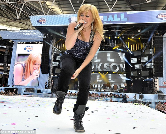 Kelly Clarkson showed off her new blonde hair and slimline figure in a pair of black trousers with a sparkly vest and black boots