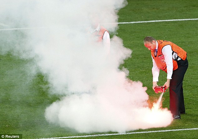 Lights out: A steward extinguishes a flare thrown on to the pitch